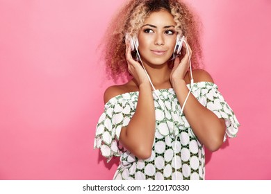 Fashion happy beautiful black woman with afro blond hair.Girl smiling and listening to music in headphones. Playful hipster model posing near pink wall