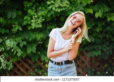 Fashion happy cool smiling girl talking on smartphone in colorful clothes oin th park wearing pink sunglasses and white t-shirt