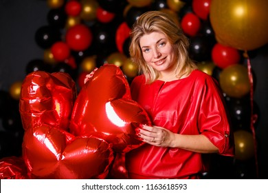 Fashion happy pretty smiling woman in red dress and with air balloons heart shape