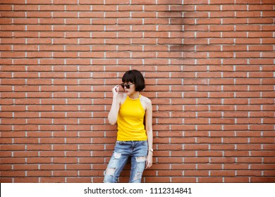 Fashion happy smiling hipster cool girl in sunglasses. Summer posing at urban brick wall background in yellow shirt, jeans and sunglasses. Copy space for text and product presentation.