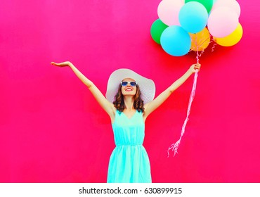 Fashion happy smiling woman with an air colorful balloons is having fun in summer over pink background