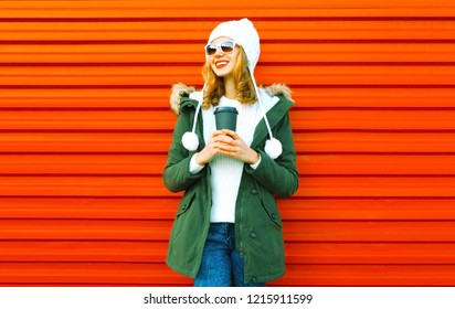 Fashion happy smiling woman holds coffee cup on red wall background