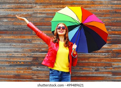Fashion happy woman with colorful umbrella in autumn day over wooden background wearing a red leather jacket