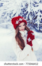 Fashion happy woman in knitted red hat having fun in winter forest