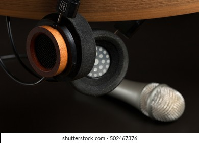 Fashion headphones on a wooden stand and studio microphone on a black background. Music concept.