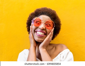 Fashion hippie african woman smiling and wearing sunglasses with yellow ochre wall in background - Black afro girl having fun - Focus on face - Youth lifestyle, trendy and happiness concept