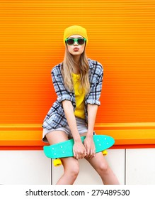 Fashion hipster cool girl in sunglasses and colorful clothes with skateboard having fun against the orange wall