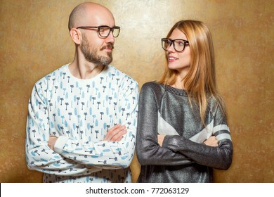 fashion hipster couple in love in glasses posing on a gold background. The concept of St. Valentine's Day.