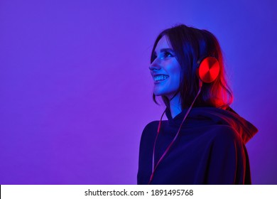 Fashion hipster girl smiles and wear headphones listening to music over color neon background at studio.