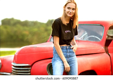 Fashion hipster girl standing near red retro car