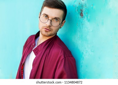 fashion hipster guy in glasses poses near the wall the color of the sour wave