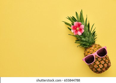 Fashion Hipster Pineapple. Bright Summer Color. Tropical Fruit with Sunglasses. Creative Art concept. Minimal style. Hot Beach Vibes. Party Mood on Yellow.