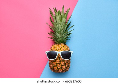 Fashion Hipster Pineapple. Bright Summer Color. Tropical Fruit with Sunglasses. Creative Art concept. Minimal style. Hot Beach Vibes. Party Mood on Pink Blue.