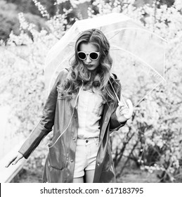 Fashion hipster woman dj with umbrella and headphones walking in park. Black and white. photo
