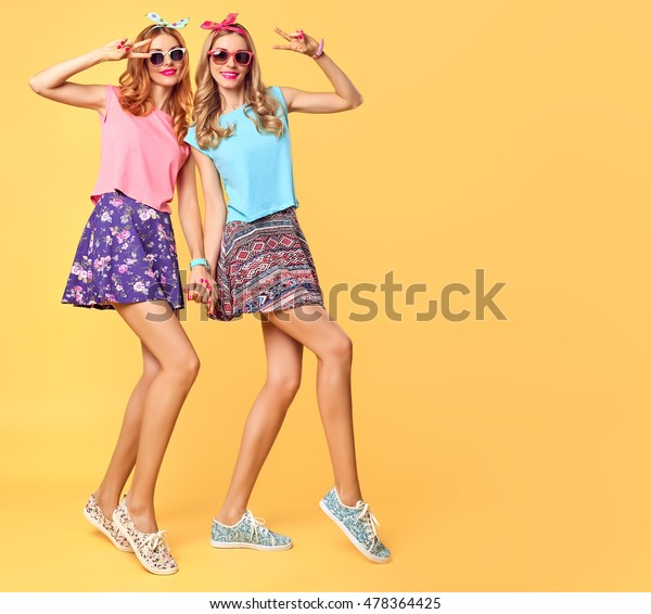 Fashion Hipster woman Having Fun Crazy Cheeky Dance. Hipster Sisters in Stylish Summer Outfit. Funny Model Girl in Sunglasses. Glamour  Trendy Hairstyle