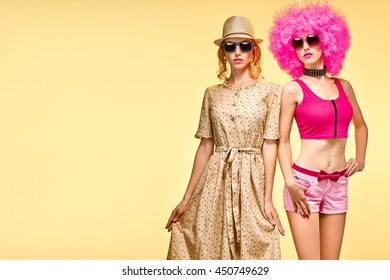 Fashion Hipster woman in Stylish Summer Outfit Having Fun. Hipster sisters best friends crazy cheeky Dance. Funny Girl in sunglasses. Glamour Trendy Hairstyle, dancing.Unusual Creative