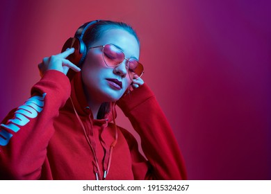 Fashion hipster woman wear stylish glasses and headphones listening to music over color neon background at studio.