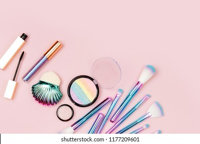 Fashion holographic colored makeup brushes with eye shadow and powder  on a pastel pink background. Flat lay, top view