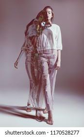Fashion, idea. Fashionable woman walking in striped pants in studio