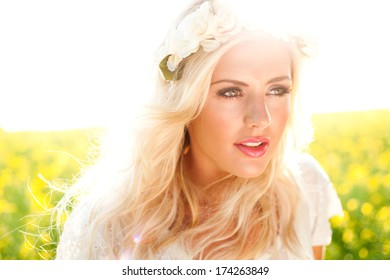 Fashion image of beautiful woman in rapeseed field, wearing flowers in hair