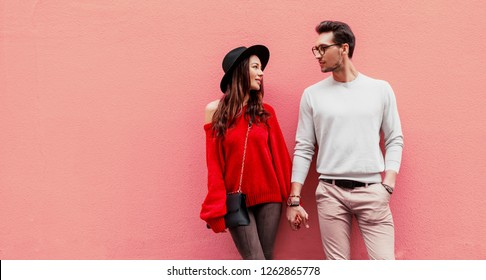 Fashion image of elegant stylish couple in love holding hands and looking on each other with pleasure. Long haired woman in red knitted sweater with her boyfriend posing on pink background.