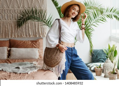 Fashion image of stylish brunette woman  posing at home in boho style. Light natural colors. Palm trees, macrame and home decor.