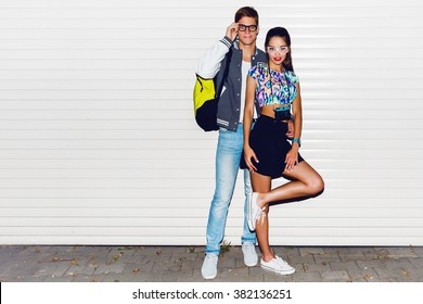 Fashion image of  stylish young  couple in love , tourists , posing near white urban wall. Wearing cool spring clothes, vintage camera,  bright neon back pack , sneakers.