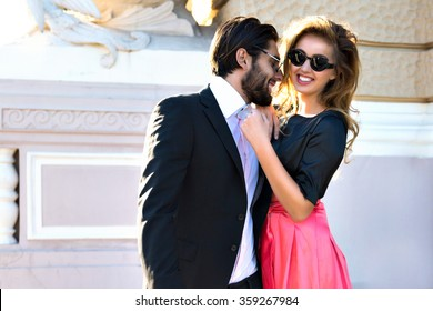 Fashion image of young blonde woman posing with her boyfriend on the street, old european city center, luxury glamour clothes, elegant couple in love, happy time, vacation, joy.