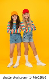 Fashion inspired by the sneaker culture. Happy kids keeping arms crossed with fashion look. Fashion small girls in casual wear smiling on yellow background. Streetwear fashion for little children.