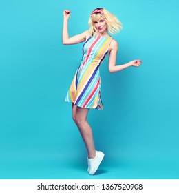 Fashion. Inspired Young blonde woman laughing dance in Studio. Lovable joyful hipster Girl Having Fun, Stylish fashionable striped dress, summer outfit. Happy dancing concept