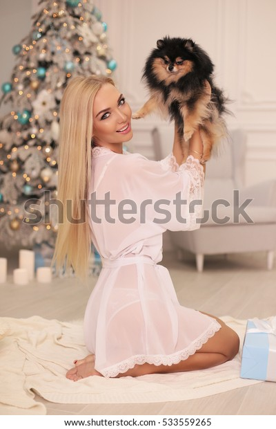 fashion interior holiday Christmas photo of beautiful woman with blond hair in cozy home clothes celebrating New Year holidays, posing with small cute dog