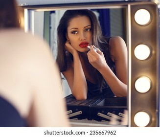 fashion interior photo of beautiful sensual woman with dark hair doing makeup in makeup room,looking at the mirror