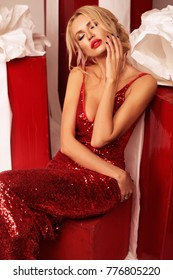 fashion interior photo of beautiful sexy woman with blond hair in elegant dress posing near big presents