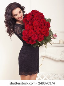 fashion interior photo of beautiful smiling woman with dark hair in elegant lace dress, holding a big bouquet of red roses