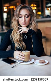 fashion interior photo of beautiful woman with blond curly hair in elegant dress and accessories, sitting in cafe, drinking a coffee with dessert