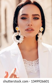 fashion interior photo of beautiful woman with dark hair in elegant white suit and accessories walking by the spring street