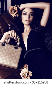 fashion interior photo of beautiful woman with dark curly hair and evening makeup,wears elegant dress, holding bag in hands