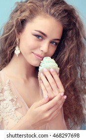 fashion interior photo of gorgeous bride with dark curly hair in luxurious wedding dress, eating sweets