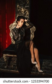 fashion interior photo of gorgeous sexy woman with dark hair in luxurious lace dress posing in theater interior, sitting in antic style chair