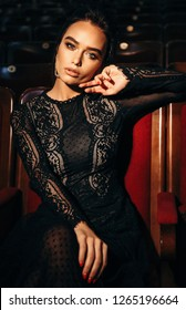 fashion interior photo of gorgeous sexy woman with dark hair in luxurious lace dress posing in theater interior