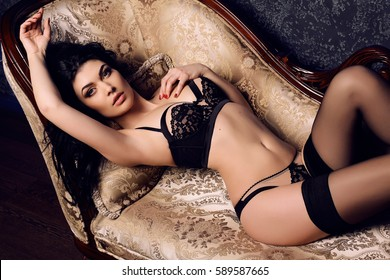 fashion interior photo of gorgeous sexy girl with dark hair in lingerie and pantyhose posing in bedroom