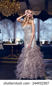 fashion interior photo of gorgeous woman with blond hair in elegant dress posing in luxury interior restaurant