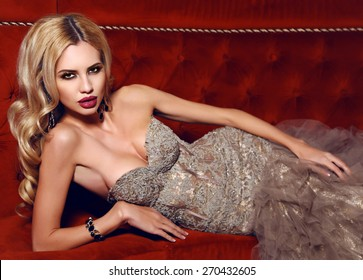 fashion interior photo of gorgeous woman with blond hair in elegant dress lying on red divan  in luxury interior