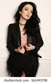 fashion interior photo of gorgeous woman with dark hair and evening makeup, in elegant clothes