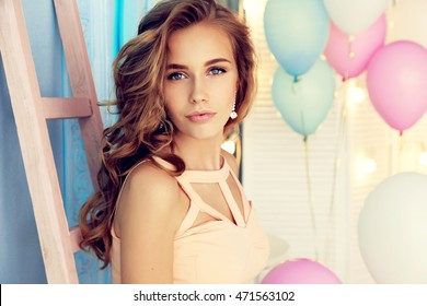 fashion interior photo of gorgeous young woman with dark curly hair wearing elegant clothes, holding air balloons