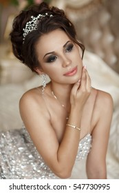 Fashion interior photo of gorgeous young bride with dark curly hair and evening makeup wears luxurious dress. Beauty model woman in lace wedding dress in diamond crown in hair studio portrait.
