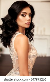 fashion interior photo of gorgeous young woman with dark hair in luxurious beige dress posing at bedroom