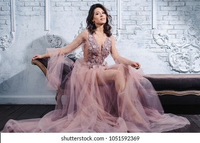 Fashion intimate vogue portrait of young brunette model woman on vintage couch wearing a floral silk violet pink robe boudoir dress provance style. White background with loft bricks texture