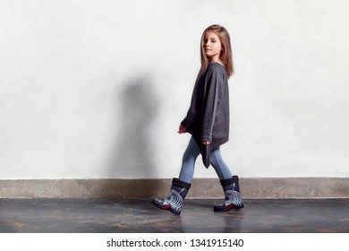 Fashion kid casual stylish clothes. Model child walks, pose. little girl poses near white wall, wears leggings, sweater, rubber boots. Full length portrait . Copy space