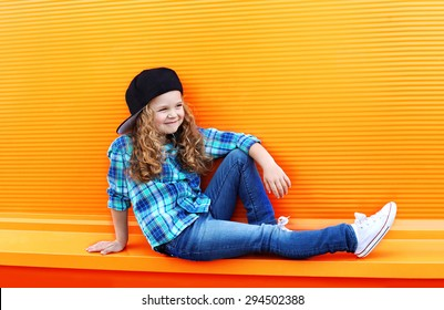 Fashion kid concept - stylish little girl child wearing a shirt and cap in the city against the colorful wall